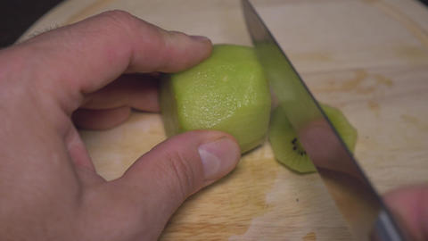 Male hands cut kiwi into several parts. For a healthy diet. close-up Footage
