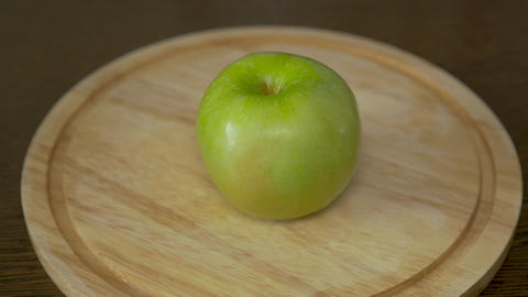 Men's hands cut the green apple into four equal parts. These are vitamins and a Footage