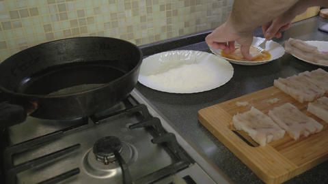 A man is cooking fish fillets at home in the kitchen Live Action