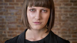 Serious young woman with short haircut looking at camera, isolated on brick Footage