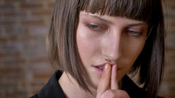 Young thoughtful woman with green eyes touching her lips looking at camera and Footage