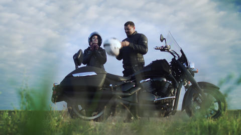 Man help his girl with helmet of motorcycle, couple preparing to ride Live Action