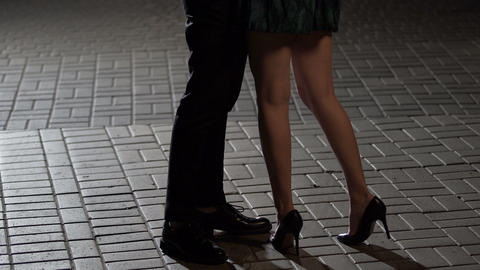 Loving couple hugging and kissing in night street, view of legs, relationship Footage