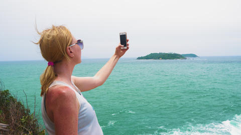 girl tourist taking pictures of the sea and the island on a smartphone. tropical GIF