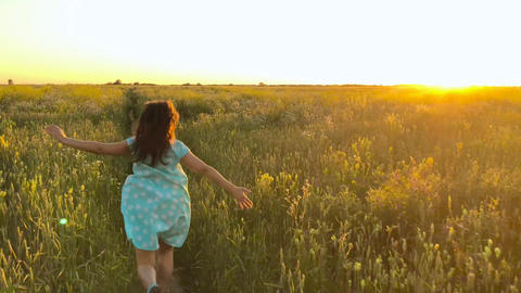Beauty girl running on green wheat field over sunset sky. Freedom concept. Wheat Footage