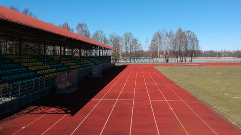 Athletic running track and tribune in small stadium in spring, aerial view Live Action