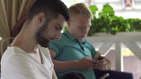 Two young men looking on mobile telephones screen sitting in restaurant Footage