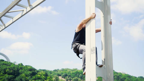 Guy climbs down from the bridge Live Action