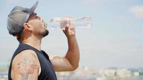 Guy in a cap and with a tattoo is drinking water Live Action