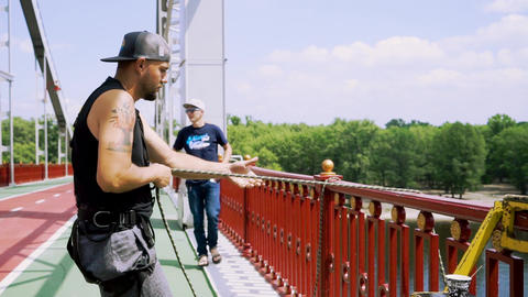 Guy in the cap on the bridge pulls up the rope Live Action