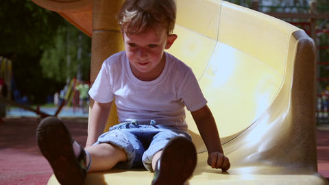 Funny toddler boy slides on a slide Live Action