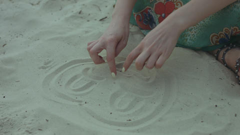 Female hands drawing funny faces on the sand on beach GIF