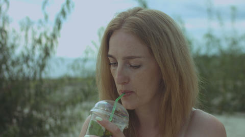 Charming redhead woman drinking cold drink on beach GIF