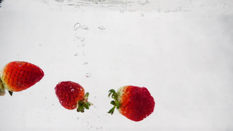 Strawberries fall into the water with bubbles. Video on isolated white Footage