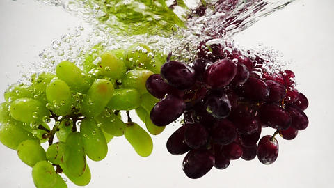 Red and green grapes falling into water with bubbles in slow motion. Fruit on Footage
