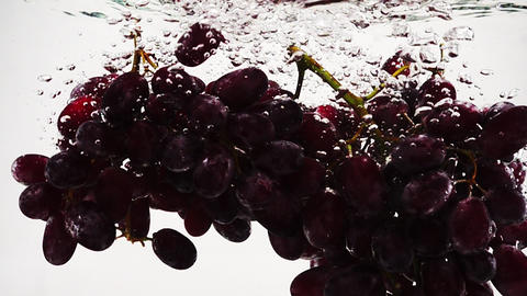 Bunch of red grapes falling into water with bubbles in slow motion. Ripe berries Footage