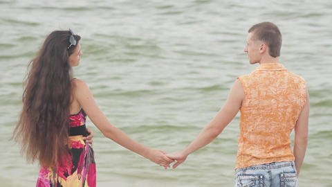 young woman and man holding hands against the sea Footage