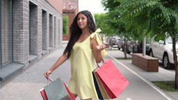 happy young girl with dark hair in a yellow dress is happy after shopping with a Footage
