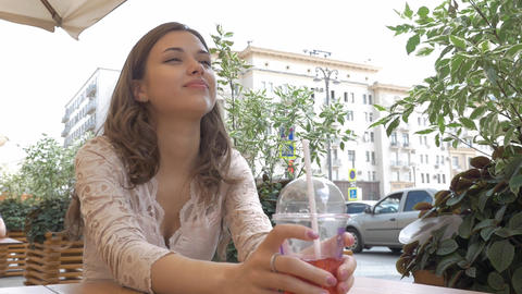 Young beautiful brunette drinks a summer cocktail while sitting at a table in a GIF