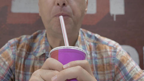 A middle-aged man drinks a milkshake Stock Video Footage