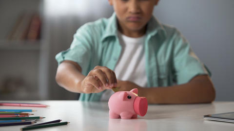 Little boy putting pocket money in piggy bank, raising funds for desired toy Live Action