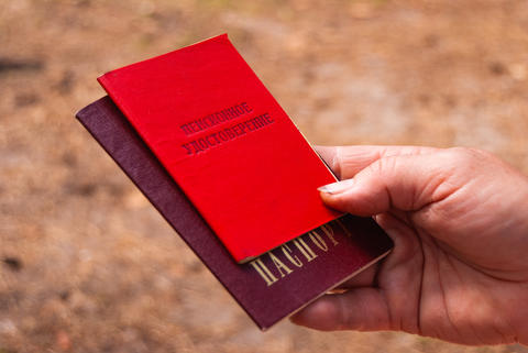 hand of the person holding the passport and pension certificate-Russian Photo