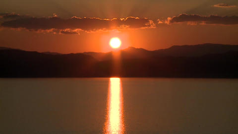 Sunset behind hills and lake timelapse Footage