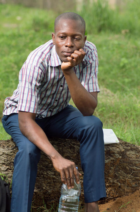Young man sitting on a tree trunk Photo