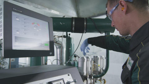 closeup employee pours liquid sample into container on liquid analyzer Live Action