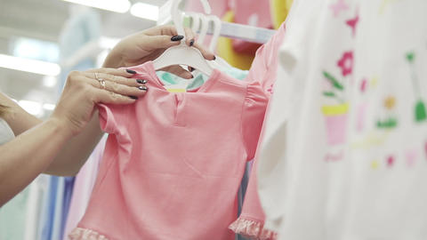Happy young woman choose clothes for their children. Beautiful woman in the Live Action