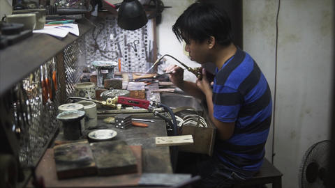 Hoi An, Vietnam - May 10, 2018: Handicrafts man repearing the parts at fair of Footage