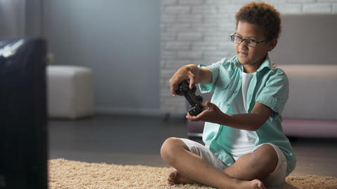 Male child behaving aggressively while losing online game, playing on console Footage