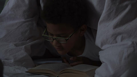 Young dreamer reading adventure books lying under blanket... Stock Video Footage