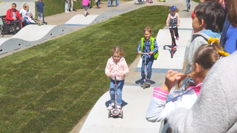 Little children ride scooters on a bike path in a park on a velodrome Live Action