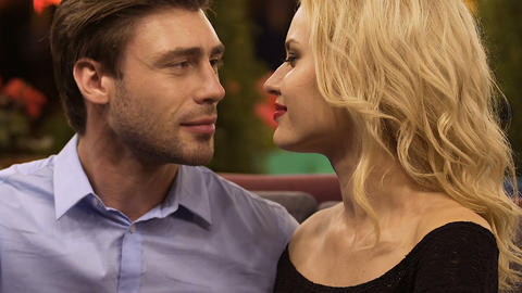 Handsome man kissing hand of blond woman, putting heads together, escort girl Live Action