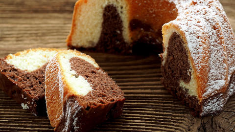 Traditional homemade marble cake. Sliced marble bundt cake on wooden table Footage