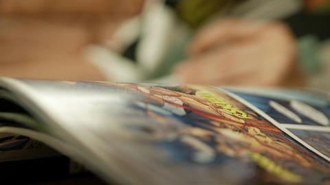 Comic book pages turning by a girl, reading a graphic novel - close-up macro GIF