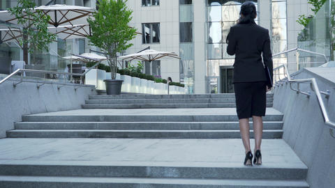 Businesswoman walking up the stairs to building, backside view, career ladder Live Action