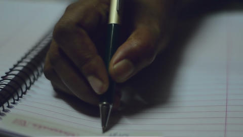 Close shot of writing using ball head pen over a spiral copy notebook Footage
