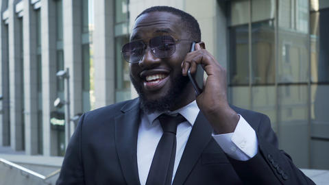 African American in business suit talking over cellphone, radiant smile, success Footage