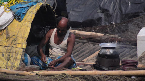 Mid Candid portrait shot of an Indian boatman over the river cooking Footage