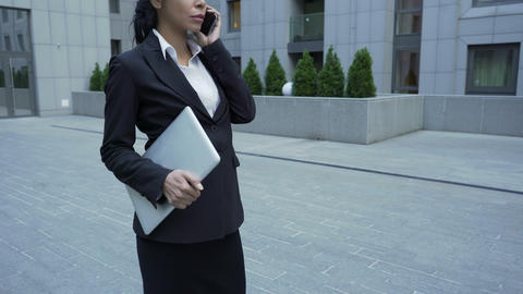 Businesswoman holding laptop and talking on cellphone, personal assistant to CEO Footage