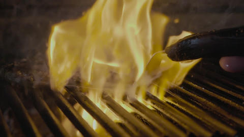 Steak slipping on the grill with fire slow mo GIF