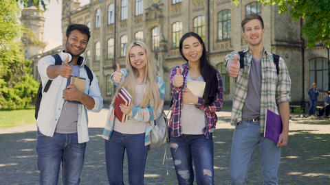 Group of multiethnic students sincerely smiling, showing thumbs-up gesture Footage
