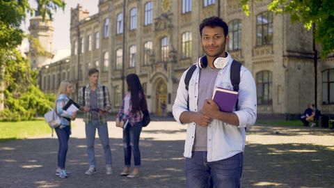 Excellent student standing near his university, sincerely smiling at camera Live Action