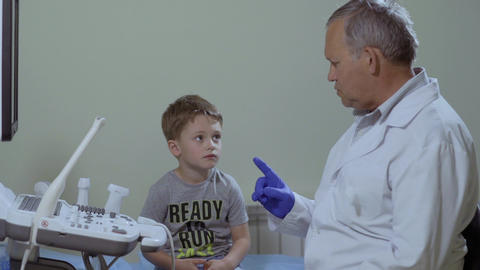 Doctor talk with little boy in the cabinet near medical ultrasound Live Action