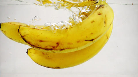 The bananas falls beautifully into the water with bubbles. Video fruits on Footage