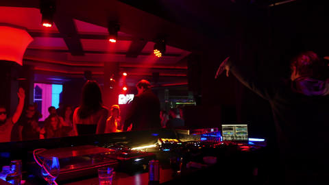 People dancing and enjoying dj mixing in night club - electronic dance techno Footage