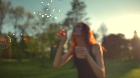Portrait of beautiful redhair young woman. Blowing bubble in the park Footage