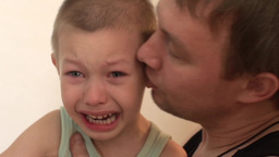 child crying angry, and beats his father,father of the child calms Footage